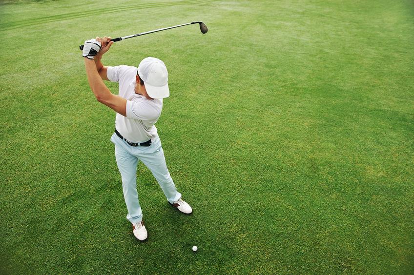 Hoge luchthoekmening van golfer die golfbal op fairway groen gras raakt