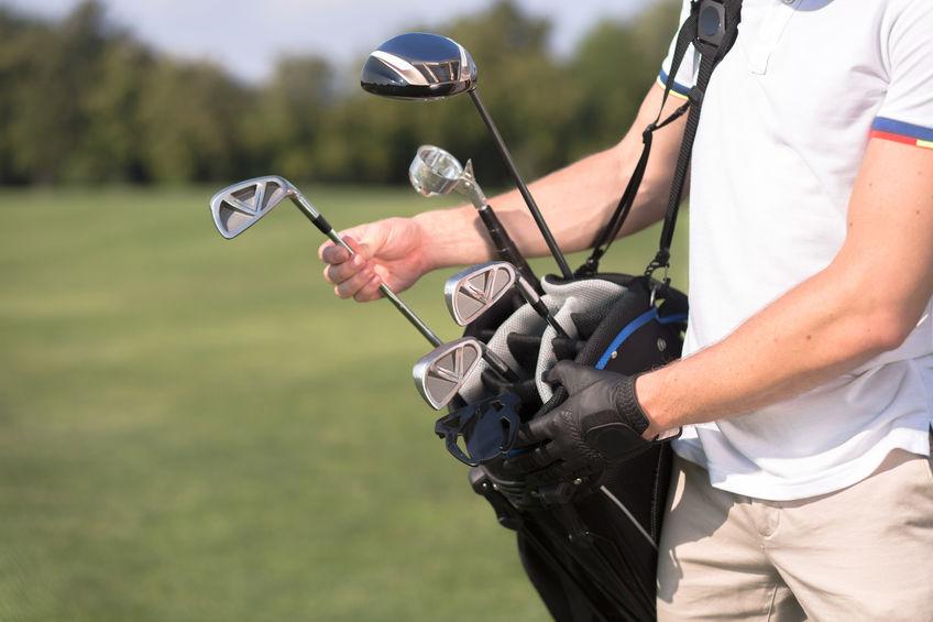 Golf en golfer concept. Man in wit T-shirt een golfclub uit zijn golftas verwijderen om te beginnen met het spelen van professioneel golf over groene baan.