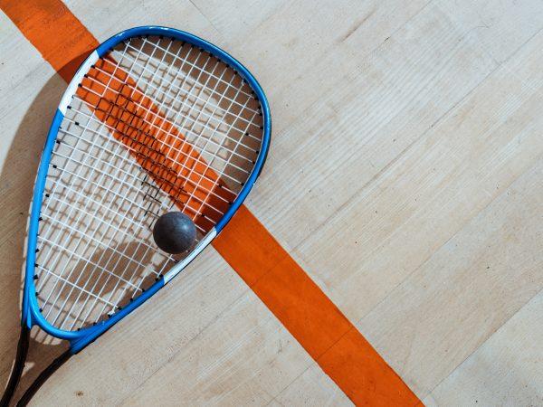 Bovenaanzicht van squash racket en bal op houten oppervlak