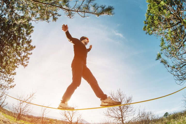 A man aged with a beard and wearing sunglasses, balances on a slackline in the open air between two trees at sunset