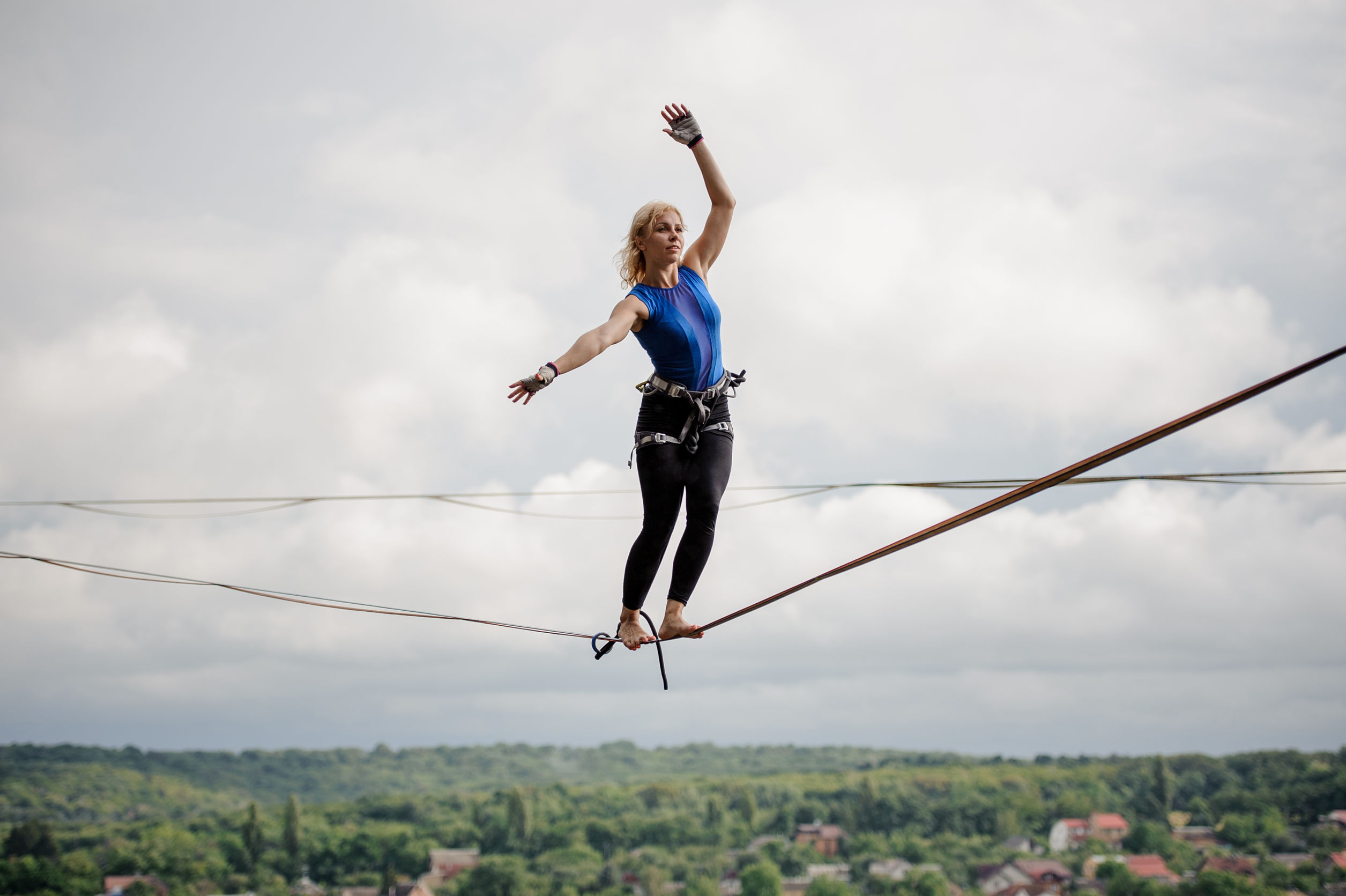 Young woman balancing tilted her hands in the right direction on the slackline