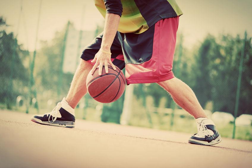 Jonge man op basketbalveld dribbelen met bal. Vintage sfeer