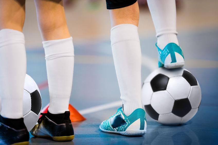 Zaalvoetballers trainen met ballen. Indoor voetbal sporthal. Voetbal zaalvoetbal speler, bal, zaalvoetbal. Sport achtergrond. Futsal competitie. Zaalvoetballers met klassieke voetbal.