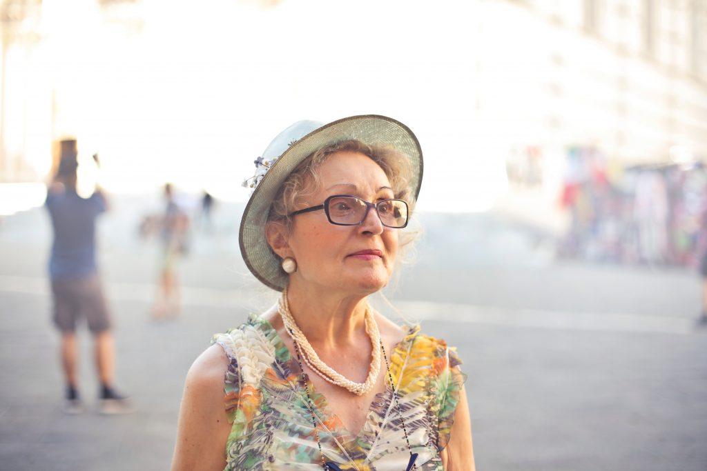 Imagem mostra uma mulher numa praça, de chapéu, brincos de pérola, vestido leve e um colar de contas.