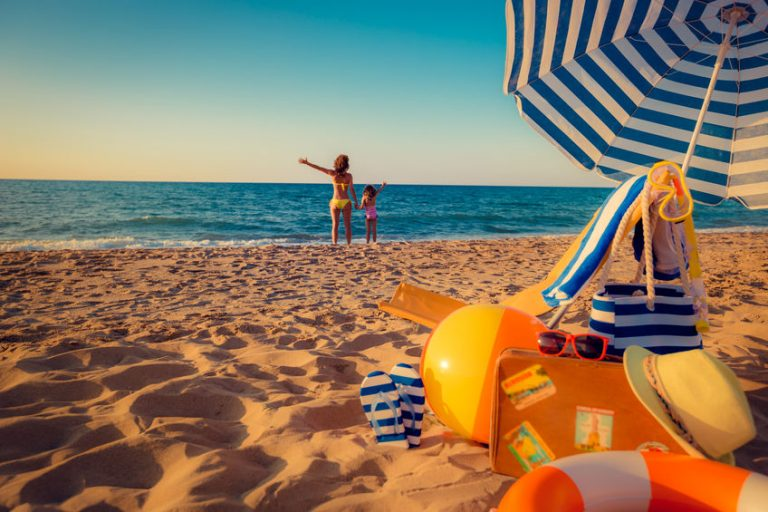 Crianças brincam na praia próximas a guarda-sol que abriga cadeira de praia e outros acessórios