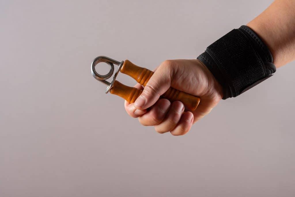 Pessoa apertando hand grip com cabo amarelo.