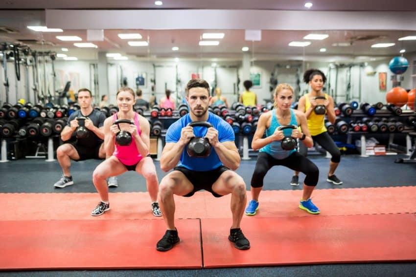 Grupo de jovens se exercitando com Kettlebell em uma sala de academia.