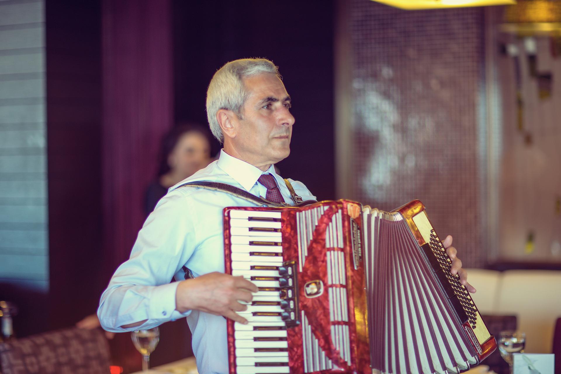 Homem grisalho com terno e gravata tocando um acordeon vermelho. Ao fundo, mostra o que parece um restaurante desfocado.