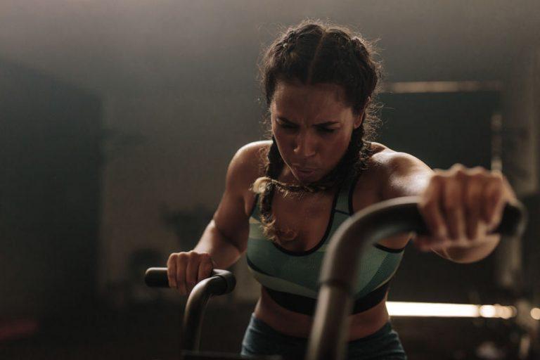 Imagem mostra uma mulher se exercitando em uma airbike.