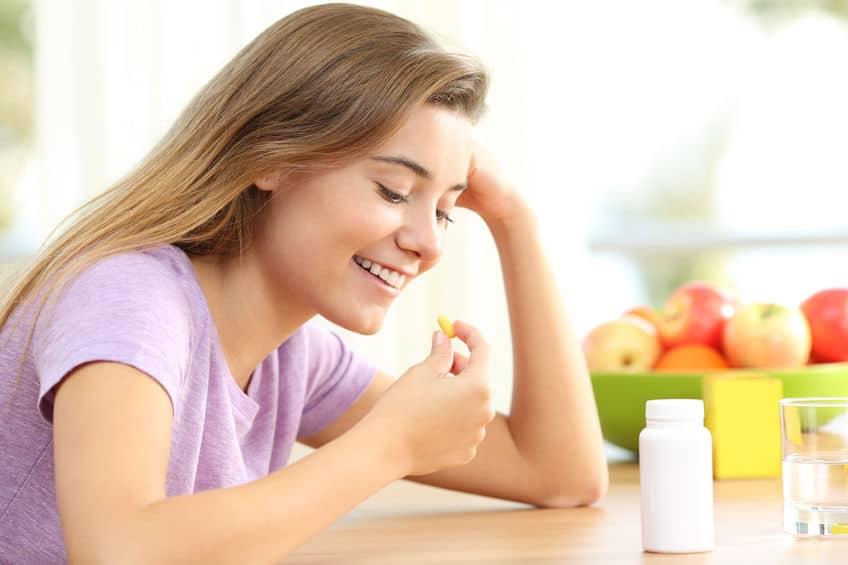 Mulher tomando comprimido de vitamina.