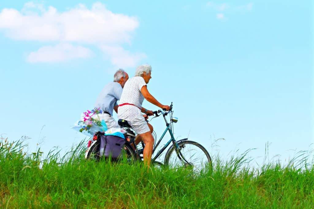 Casal de idosos andando de bicicleta.