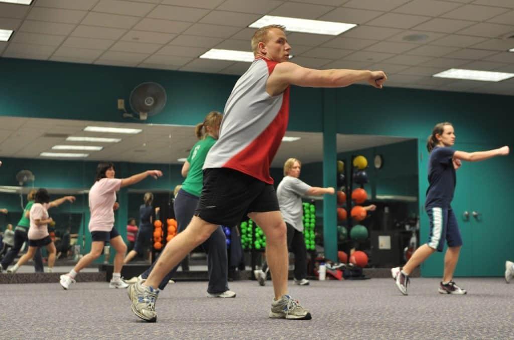 Homens e mulheres praticando ginástica em sala de academia.
