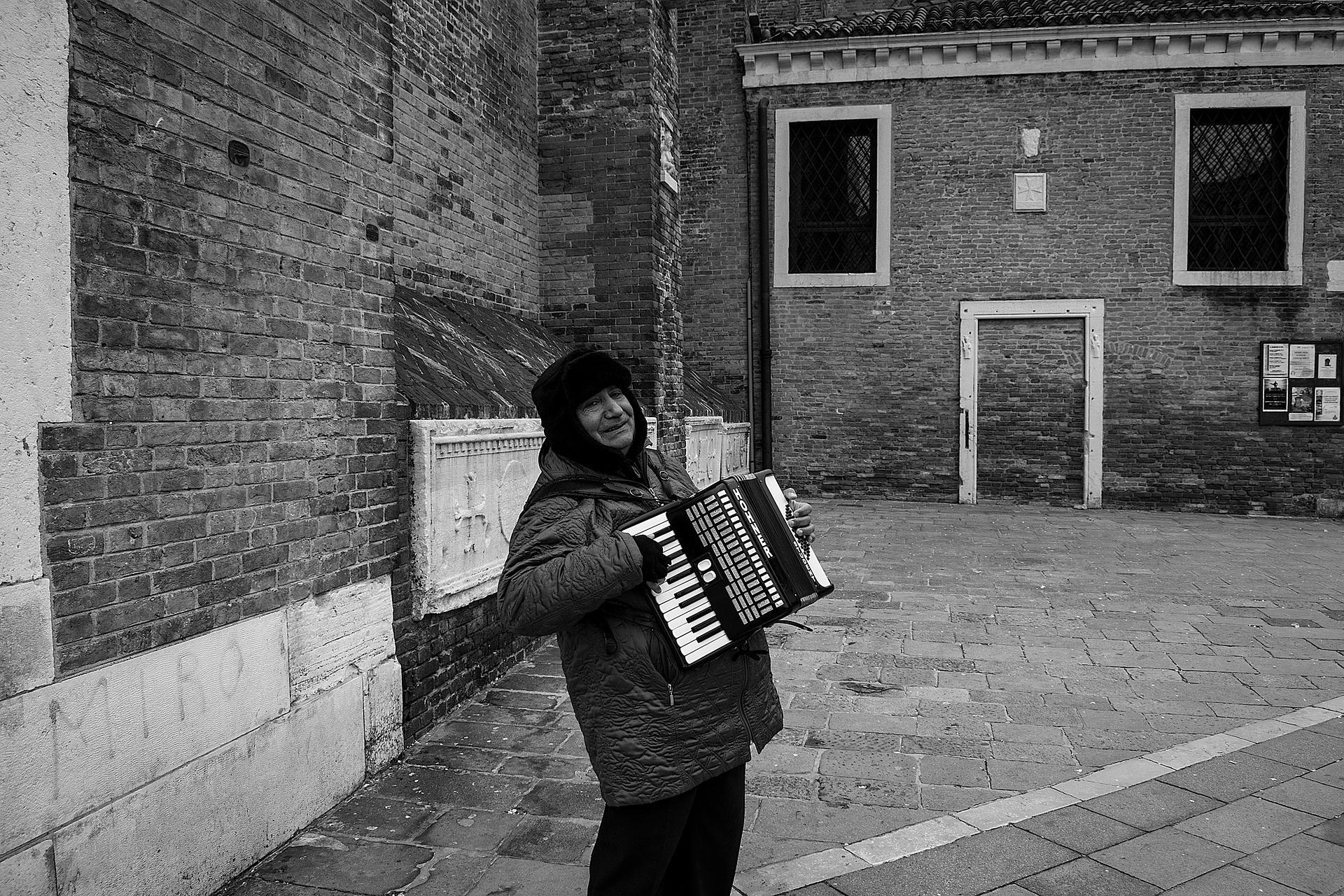 A foto em preto e branco mostra um homem com casaco pesado e touca tocando acordeon. Ao fundo, podemos ver prédios de tijolo.