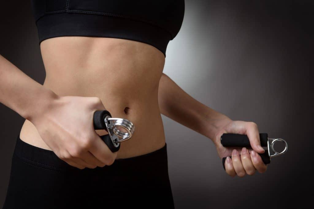 Tronco de mulher se exercitando com hand grip.
