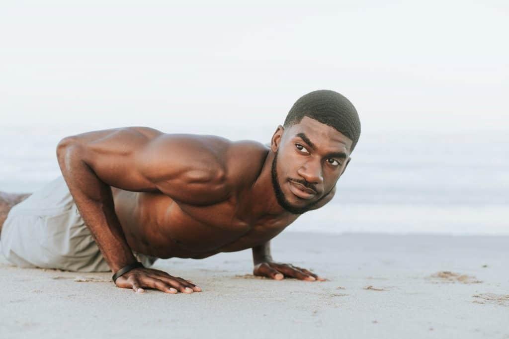 Homem fazendo flexão ao ar livre.