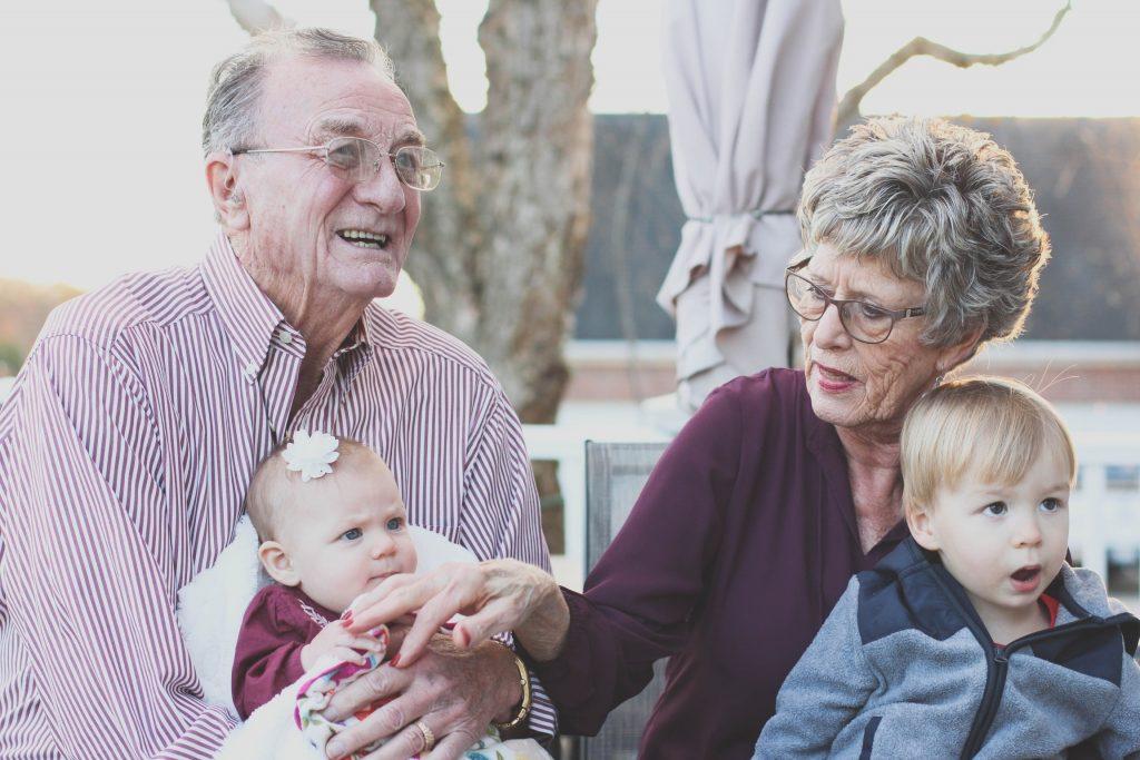Imagem mostra um casal de avós segurando seus netos, cada um no colo de um. O avô sorri, a avó mexe com a neta no colo do avô.