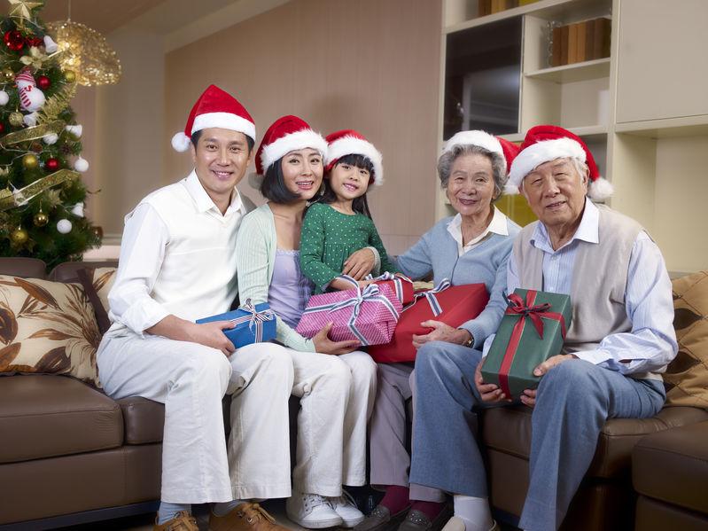 Imagem mostra uma família, com pais, avós e uma criança, todos com gorros natalinos, sentados no sofá, ao lado de uma árvore de natal decorada.Imagem mostra uma família, com pais, avós e uma criança, todos com gorros natalinos, sentados no sofá, ao lado de uma árvore de natal decorada.