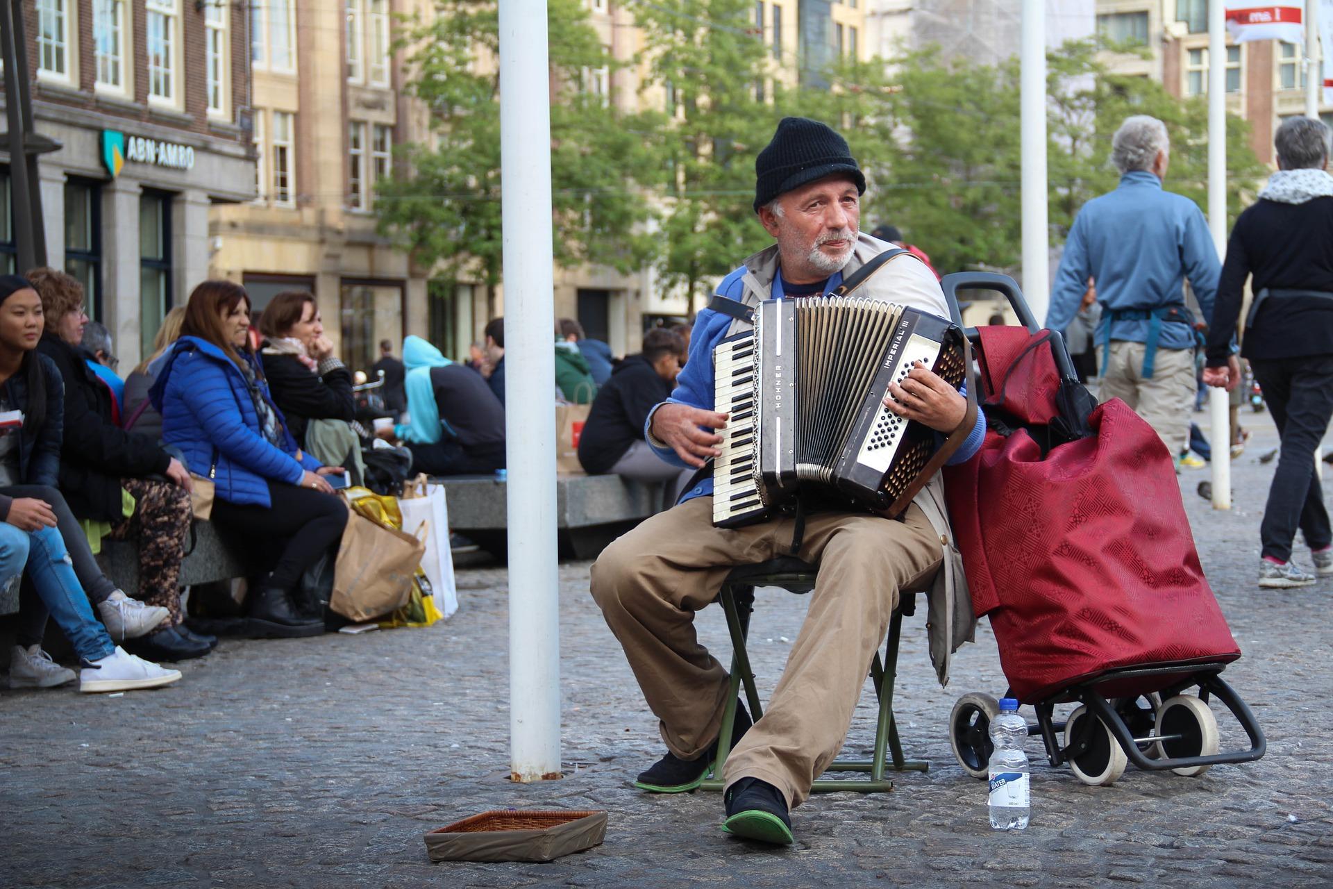 A imagem mostra um homem idoso sentado tocando acordeon em uma praça pública à luz do dia. À sua frente, há uma caixinha para as pessoas colocarem dinheiro. Ao fundo, diversas pessoas estão sentadas ou caminhando.