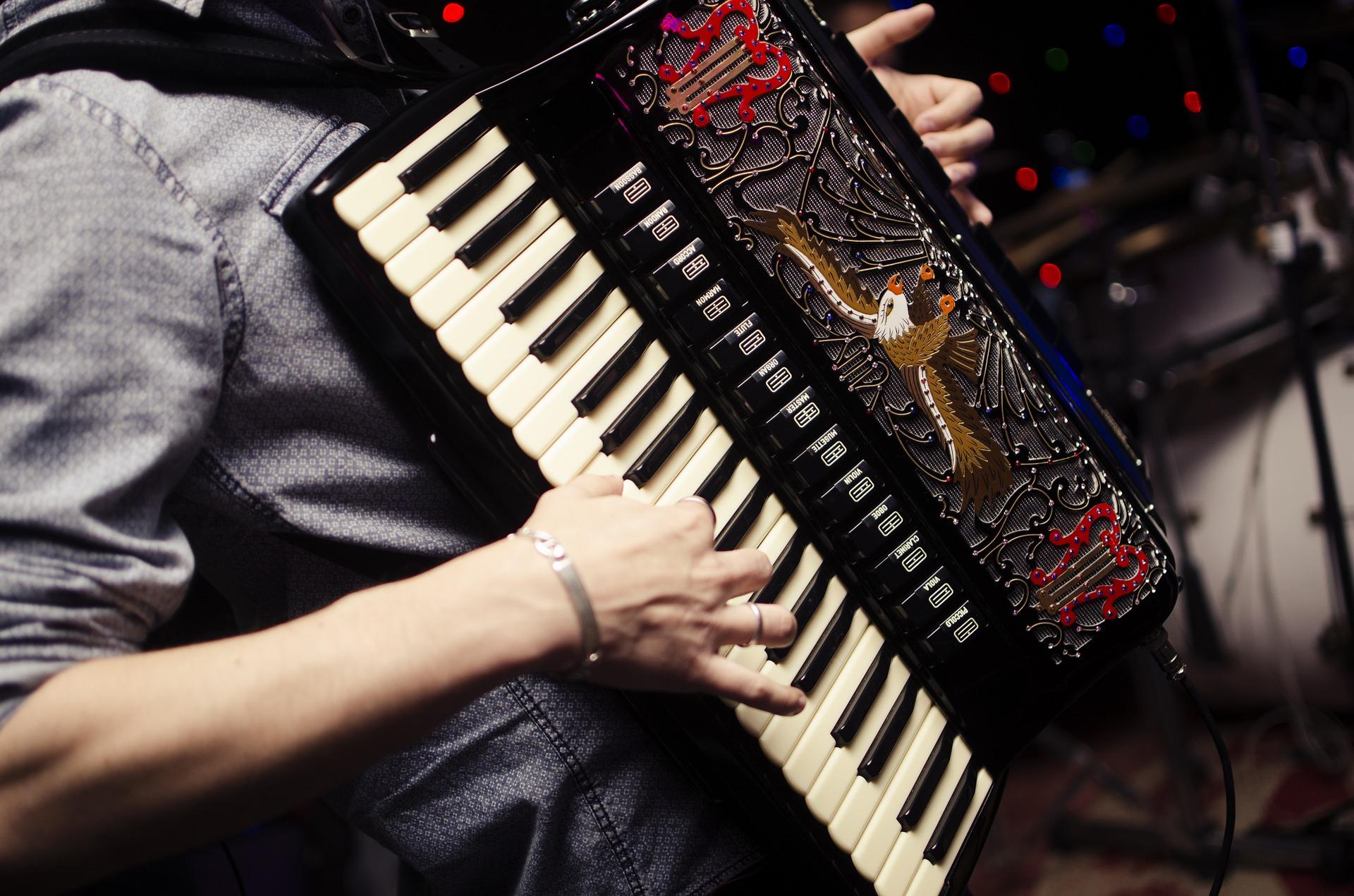 A imagem foca um acordeon de várias teclas com um detalhe em formato de águia. Uma mão está tocando-o, mas não vemos o rosto.